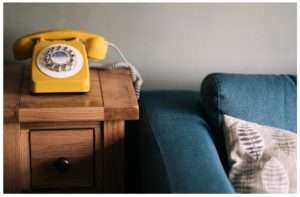 old-fashioned yellow telephone next to a green sofa